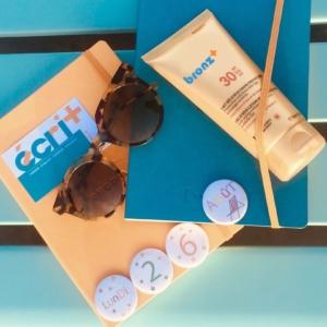 """image montrant des carnets, des lunettes de soleil, de la crème solaire """"bronz+"""", le tout aux couleurs d'écri+ : bleu et orange."""